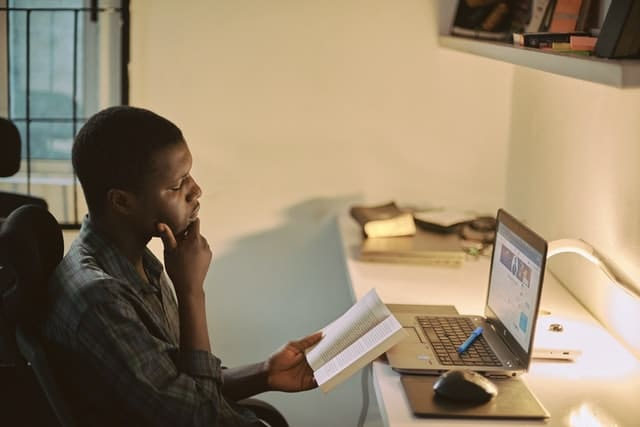 student studying with a laptop and book